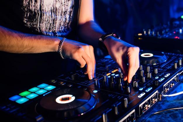 Mixer e cabina dj in discoteca con le mani del dj che mescolano musica e regolatori di controllo