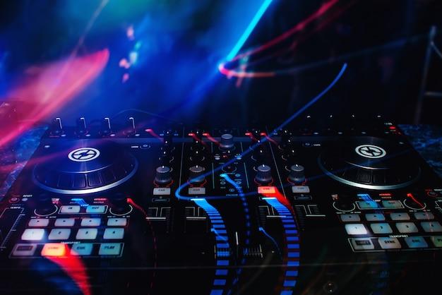 Mixer e dj stand nella discoteca alla festa c di brillanti effetti multicolori