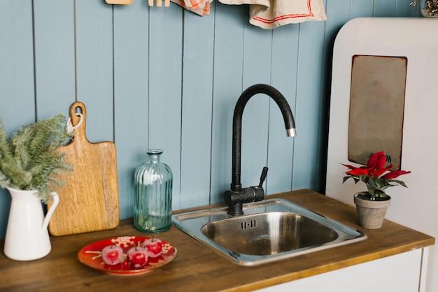 Mixer e tagliere di legno e rami in un vaso bianco in cucina, decorato per natale