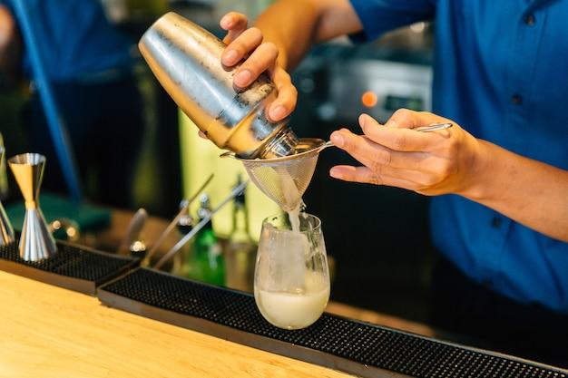 Mixologist che fa cocktail con shaker, jigger di doppia dimensione e bicchiere con cubetto di ghiaccio.