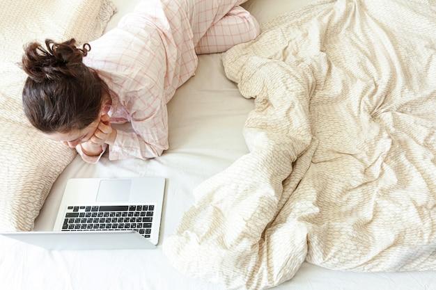 Mobile office a casa. giovane donna in pigiama che si siede sul letto a casa che lavora usando sul computer pc portatile. ragazza di stile di vita che studia al chiuso. concetto indipendente di quarantena di affari.