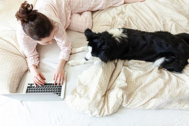 Mobile office a casa. giovane donna in pigiama che si siede sul letto con il cane che lavora usando sul computer pc portatile a casa. ragazza di stile di vita che studia al chiuso. concetto indipendente di quarantena di affari.