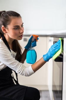 Mobilia sorridente di pulizia della casalinga della giovane donna in cucina