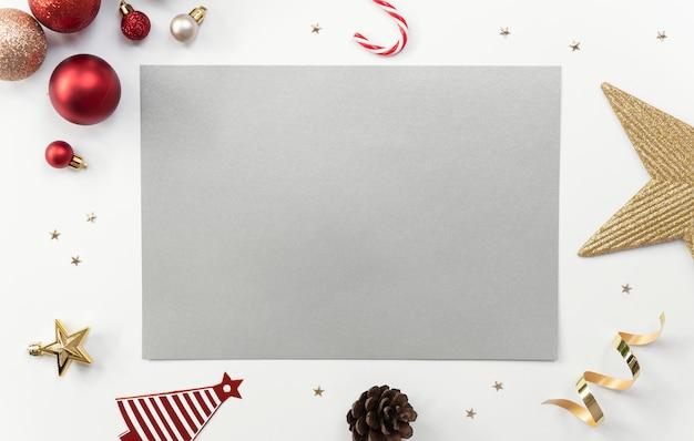 Mock up biglietto di auguri su bianco con decorazioni natalizie e coriandoli.