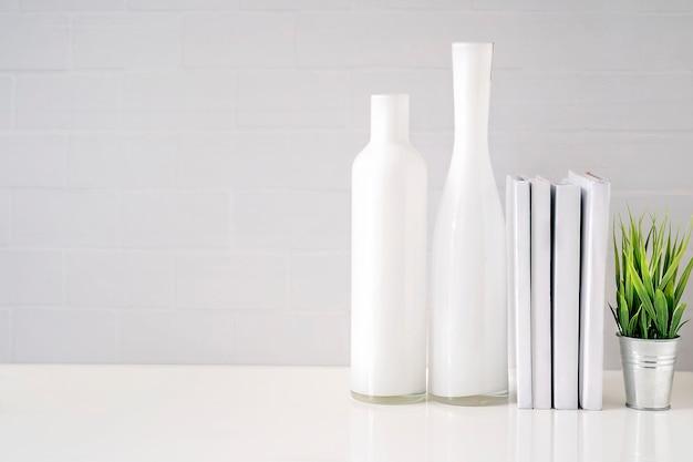 Mock up bottiglia di vetro, libri e houseplant sul tavolo bianco con muro di mattoni bianchi