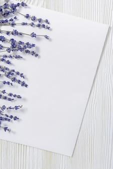 Mock-up con fiori di lavanda secchi e carta bianca bianca sulla superficie in legno