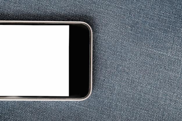 Mock up con smartphone moderno su tessile denim.