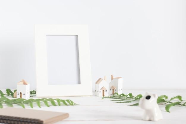 Mock up, cornice bianca vuota con foglia di felce e modello di casa bianca in miniatura su tavola di legno bianco, minimalista