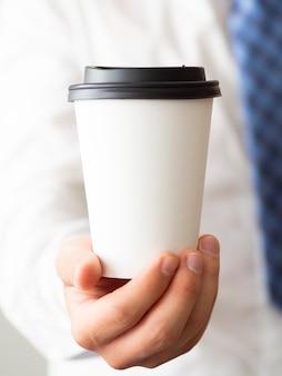 Mock-up della tazza di caffè della holding della mano del primo piano