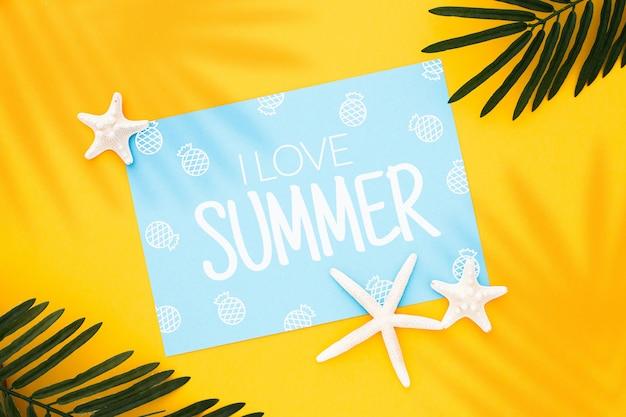 Mock up design su un'immagine di concetto di estate con foglie di palma e stelle marine su sfondo giallo
