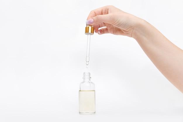 Mock-up di bottiglia di vetro contagocce. la goccia oleosa cade dalla pipetta cosmetica su fondo bianco