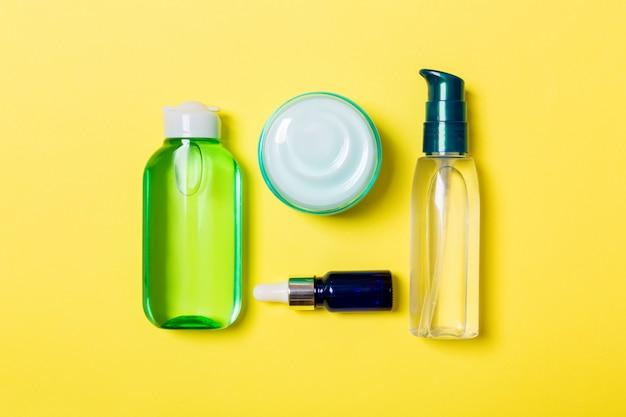 Mock-up di marchio spa di cosmetici, vista dall'alto con spazio di copia. set di tubi e vasetti di crema piatto giaceva su sfondo giallo