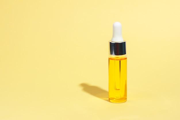 Mock-up in vetro per contagocce. cosmetici per la cura della pelle del siero su giallo