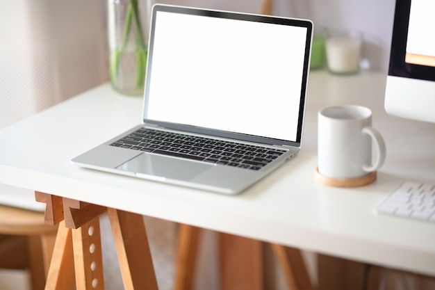 Mock up laptop schermo vuoto nello spazio di lavoro del loft