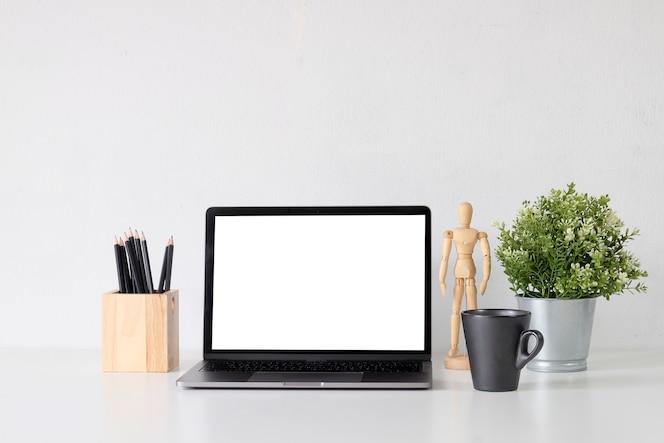 Mock up laptop su spazio di lavoro con tazza caffè, plat e barattolo di matita ufficio spazio copia.