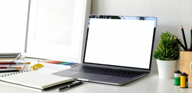 Mock up laptop sull'area di lavoro dell'artista creativo