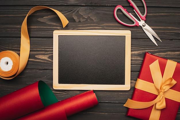 Mock-up lavagna con carta da regalo e regalo per natale
