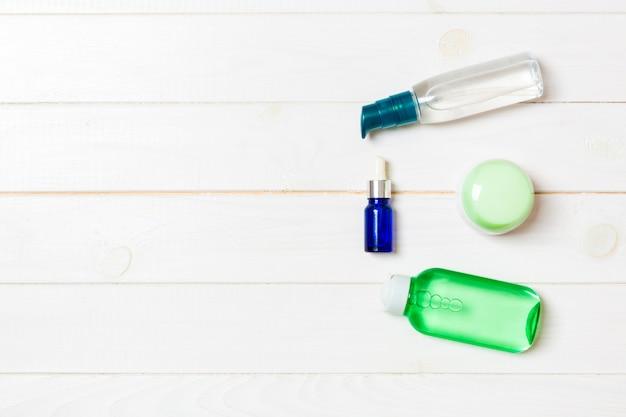Mock-up marcante a caldo della stazione termale dei cosmetici, vista superiore con copyspace. set di tubi e vasetti di crema piatto giaceva su legno bianco