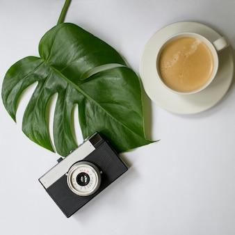 Mock up spazio di lavoro con foglia di palma tropicale, notebook, fotocamera, penna, carta e tazza di caffè