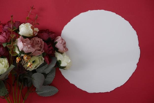 Mock-up tondo libro bianco con spazio per testo o immagine su sfondo rosso e fiore.