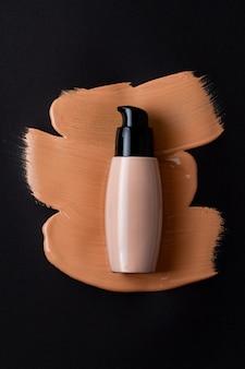 Mockup con bottiglia per fondotinta viso e goccia macchiata di correttore