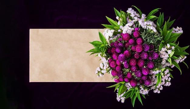 Mockup con busta di carta e fiori su sfondo scuro.