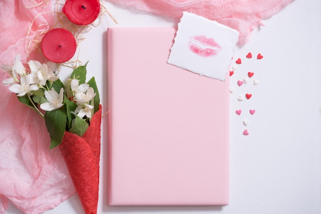 Mockup con cartolina e gelsomino su sfondo rosa. carta e fiori bianchi. cialda per gelato, bacio labbra