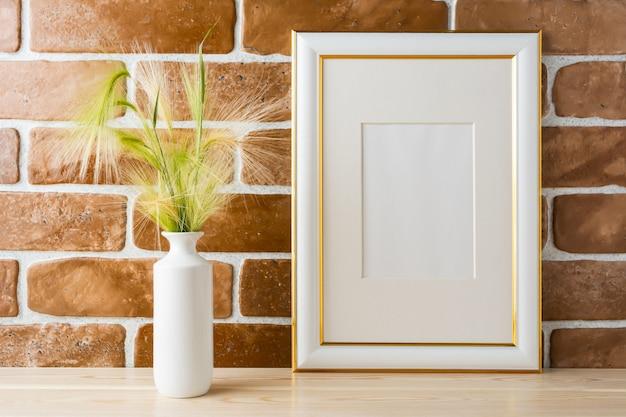 Mockup cornice decorata oro con muro di mattoni a vista erba ornamentale
