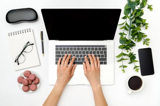 Mockup dell'area di lavoro del ministero degli interni. computer portatile con lo schermo, le mani e gli accessori in bianco su bianco