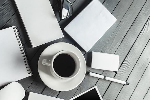 Mockup di articoli per ufficio con una tazza di caffè