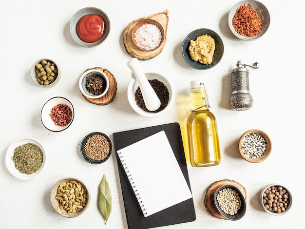 Mockup di blocco note da cucina per testo culinario, varie spezie e salse secche