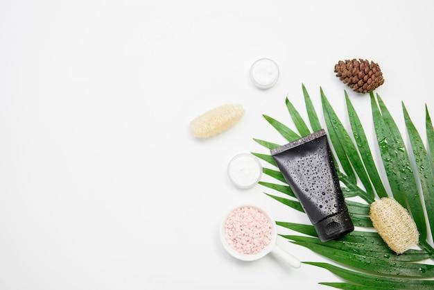 Mockup di bottiglia di crema cosmetica, pacchetto di etichetta vuota e ingredienti su uno sfondo di foglie verdi.