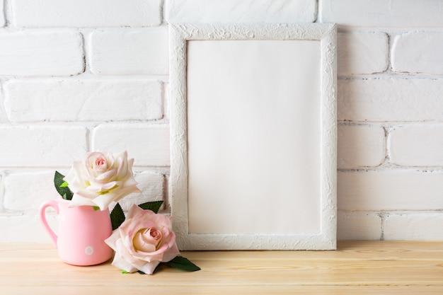 Mockup di cornice bianca con due rose rosa pallido