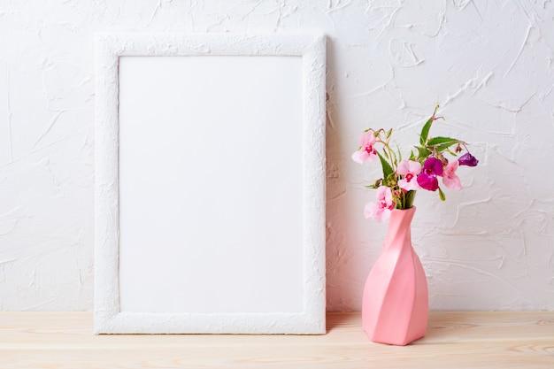 Mockup di cornice bianca con fiori in vaso rosa roteato