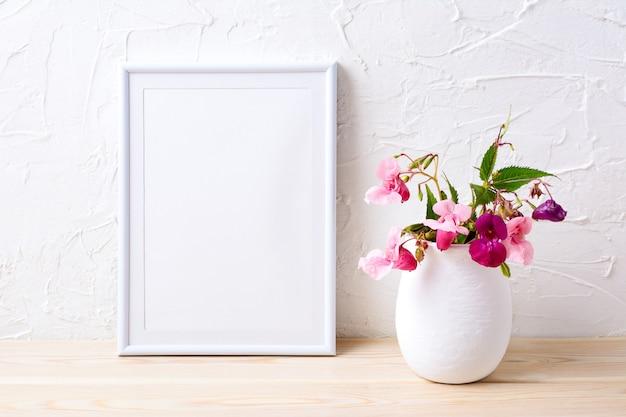 Mockup di cornice bianca con piante di casa rosa in vaso di fiori