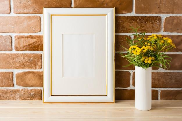 Mockup di cornice decorata oro fiori gialli vicino a muri di mattoni a vista