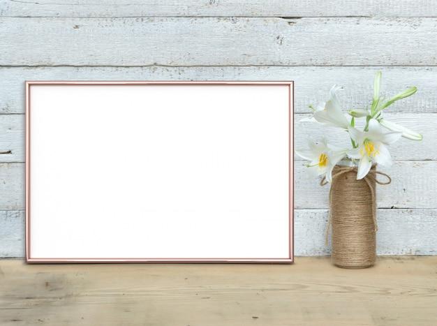 Mockup di cornice orizzontale in oro rosa a4 vicino a un mazzo di gigli si trova su un tavolo di legno