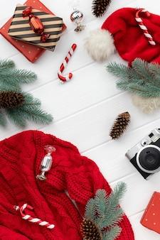 Mockup di vendita dello shopping natalizio con maglione, regali e ornamenti su fondo di legno. vista dall'alto piatto modello laico per il saluto invito