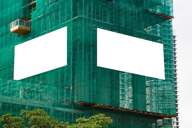 Mockup in bianco di pubblicità esterna sulla parete dell'edificio in costruzione con ponteggi