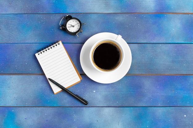 Mockup per check list, carta per appunti vuota con una tazza di caffè su legno blu. concetto di ufficio, scrittore o studio