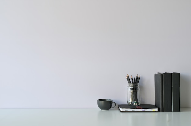 Mockup scrivania area di lavoro e copia spazio libri, caffè e matita sulla scrivania bianca.