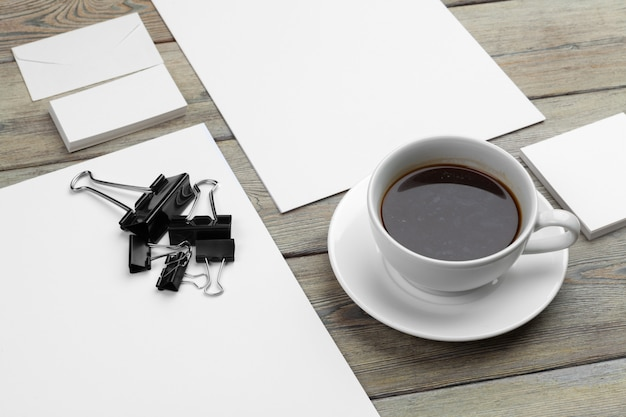 Mockup set di biglietti da visita, notebook, documenti cartacei e tazza di caffè.