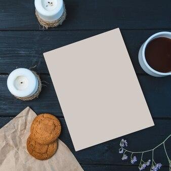 Mockup sul tema della colazione con caffè. blocco note, tazza di caffè, biscotti su un tavolo di legno copia spazio