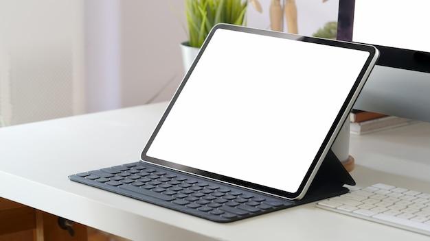 Mockup tablet computer e schermo vuoto sull'area di lavoro