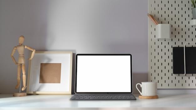 Mockup tablet con tastiera intelligente sul tavolo di lavoro minimale.