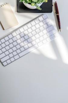 Mockup tastiera bianca e forniture sul tavolo bianco, copia spazio per testo o prodotto display.