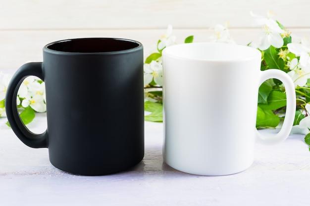 Mockup tazza bianca e nera con fiori di melo