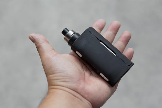 Mod di scatola nera regolata di fascia alta con atomizzatore gocciolante ricostruibile in mano su texture grigio chiaro