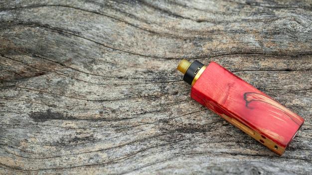 Mod di scatola regolata in legno stabilizzato naturale rosso di fascia alta con atomizzatore gocciolante ricostruibile su sfondo texture legno legno naturale, attrezzature vaporizzatore, messa a fuoco selettiva