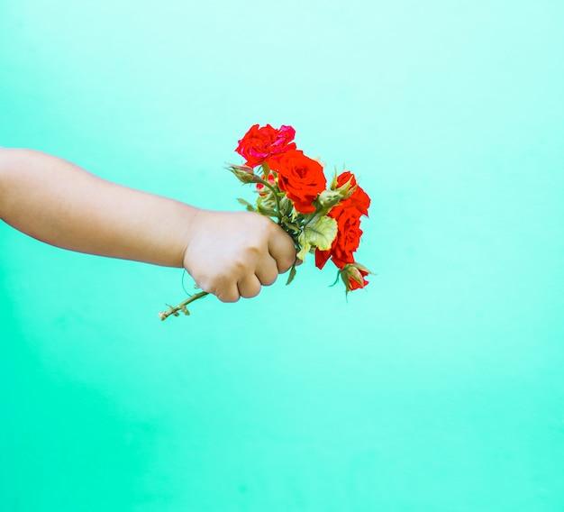 Moda arte mano di un bambino che tiene il mazzo di rose